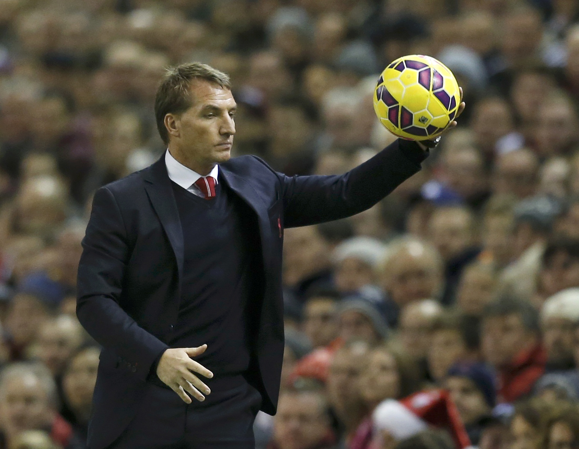 Liverpool manager Brendan Rodgers catches the ball during their English Premier League soccer match against Arsenal at Anfield in Liverpool