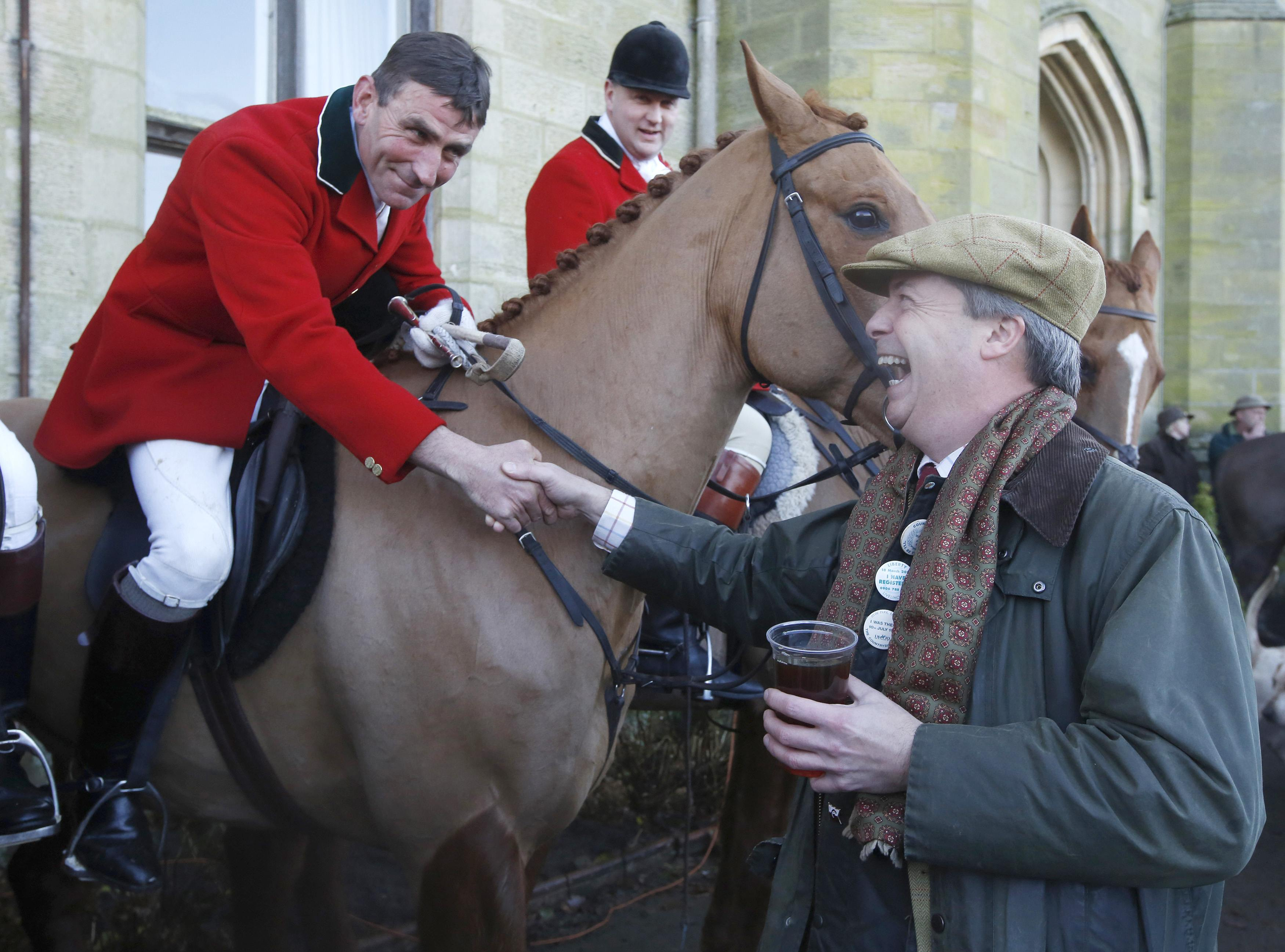UK Independence Party leader Nigel Farage shakes hands with huntsman Mark Bycroft of the Old Surrey Burstow and West Kent Hunt before they departed from Chiddingstone Castle for the annual Boxing Day hunt in Chiddingstone, south east England