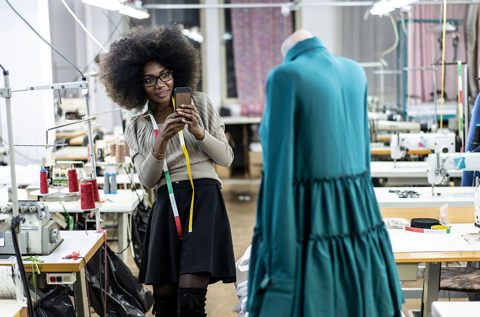 A female fashion designer with a tape measure draped over her takes a photograph of the dress that she's working on