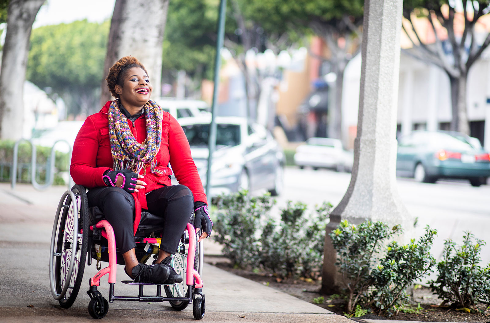 A young, disabled Black woman in a wheelchair wearing a red sweater explores a city