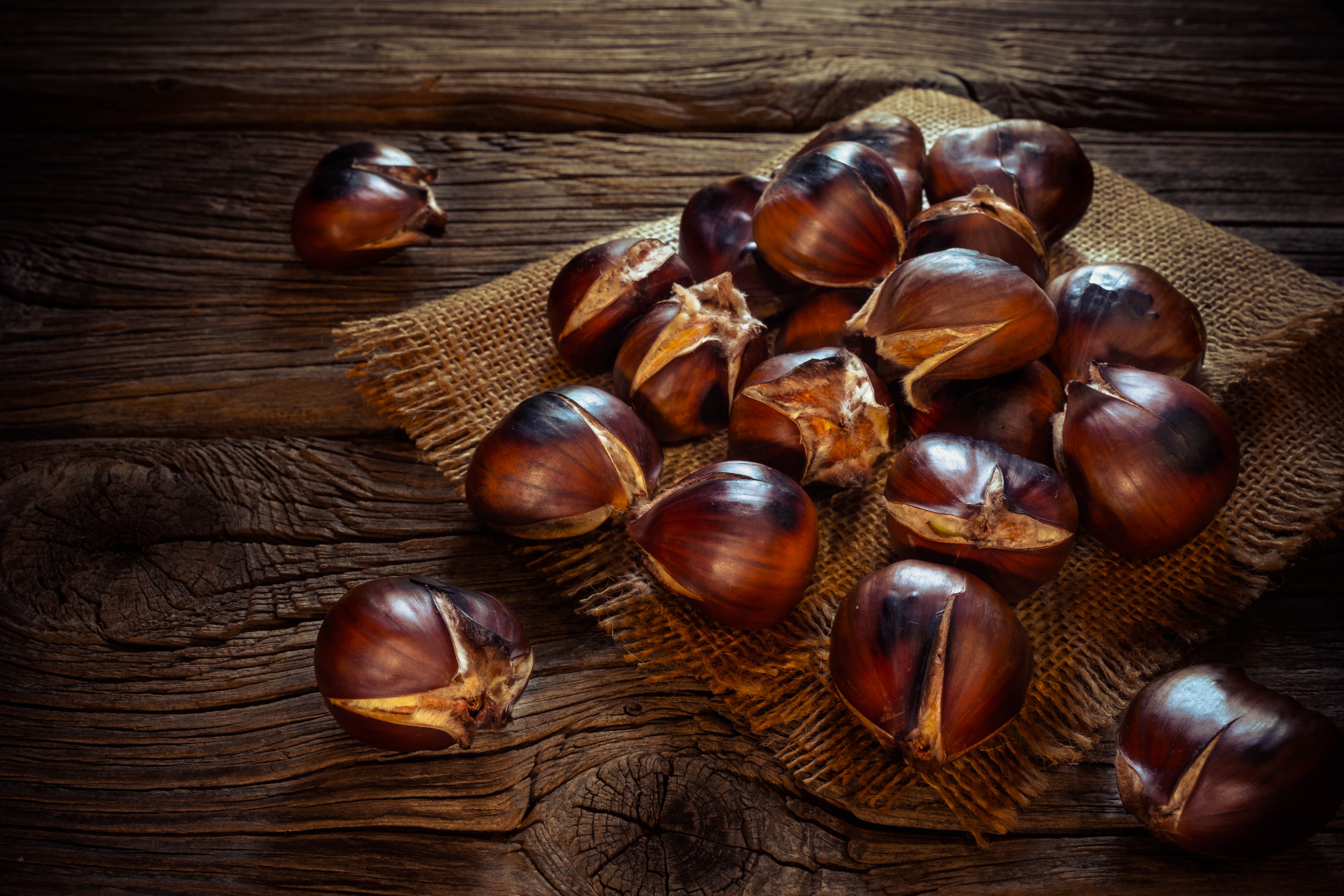 Roasted chestnuts on a sack napkin and wooden background