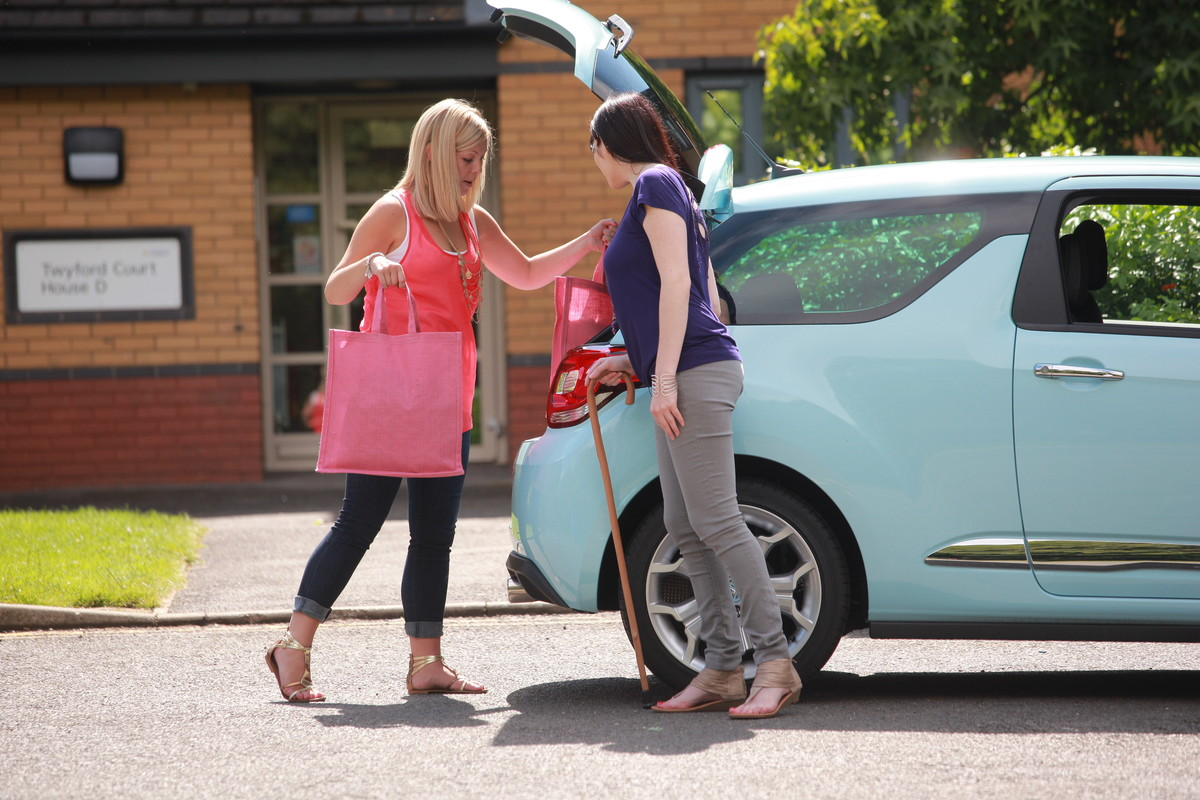 Woman putting shopping in car boot