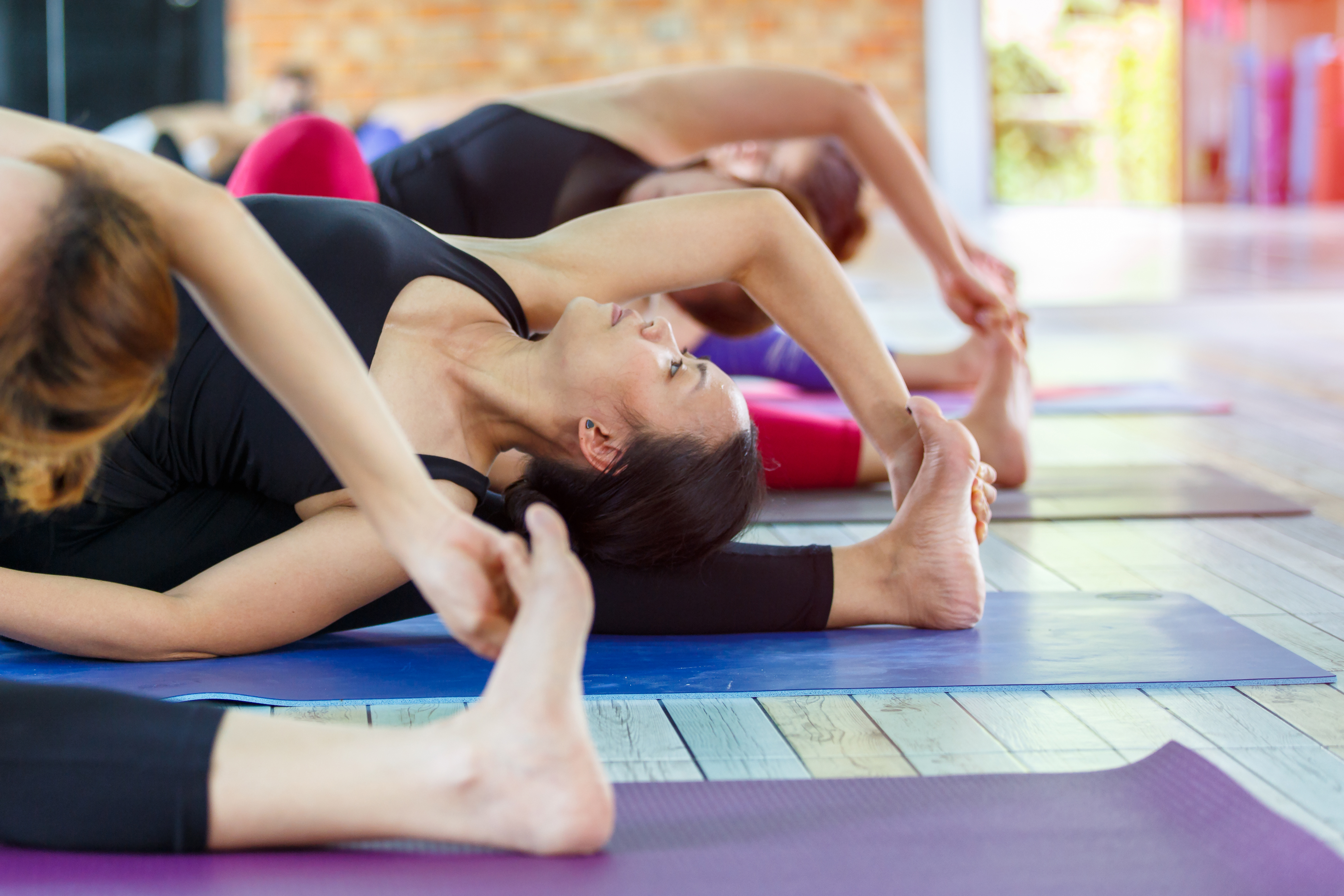 Fitness asian female group doing warm up yoga pose