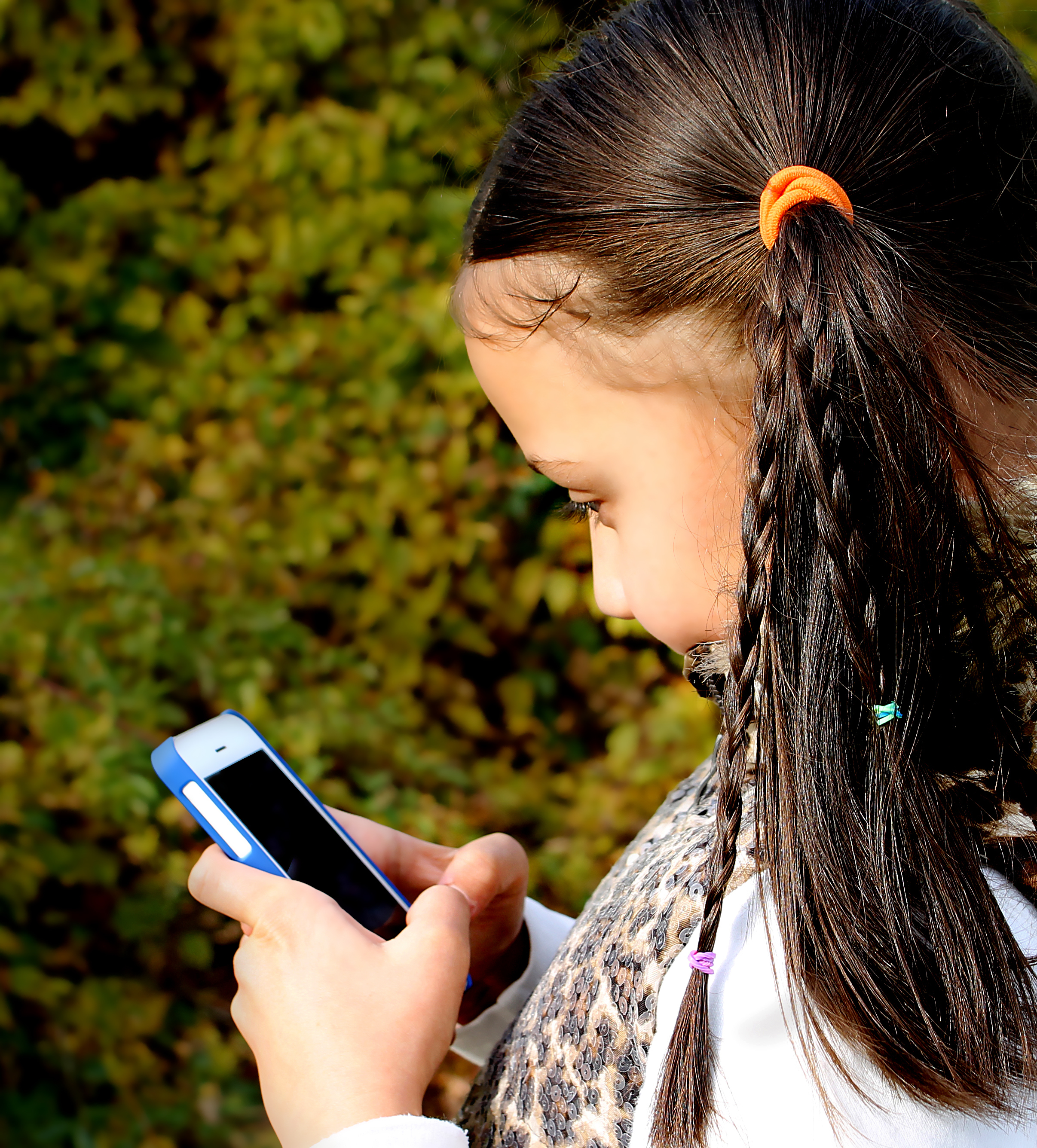 Little girl with ponytails using cell phone in the park.