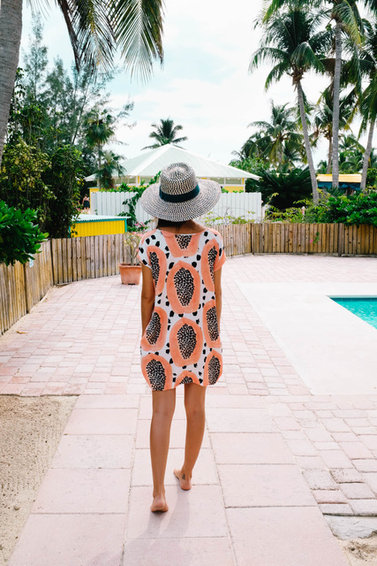Drea walking by pool in patterned dress